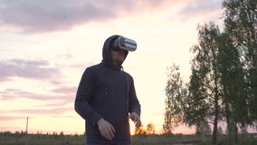 Young man using VR 360 headset and having vitrual reality experience at city park on sunset stock video footage