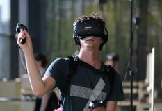 Young man using VR set at sonar festival with hand handles. People test different virtual reality models and environments during sonar advanced music and arts in Royalty Free Stock Photos