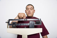 Young Man Using Weight Scales Royalty Free Stock Photography