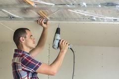 Young man in usual clothing and work gloves fixing drywall suspended ceiling to metal frame using electrical screwdriver on royalty free stock image