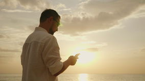 A young man on vacation near the sea. Using a smartphone at sunset. 4K slow motion video stock footage