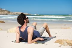 Young man on vacation sitting alone at a secluded beach Stock Photos