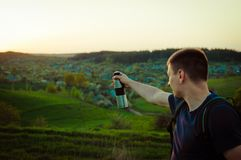 Travelling hiking backpacking sunset success inspiration. Young man with vacuum flask in the hand point with finger a way. Concept of the travelling, backpacking Royalty Free Stock Photography