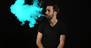 Young man vaping with an electronic cigarette and make some BLUE smoke clouds Royalty Free Stock Photography