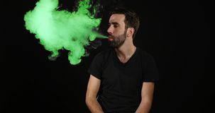 Young man vaping with an electronic cigarette and make some green smoke clouds Stock Photography