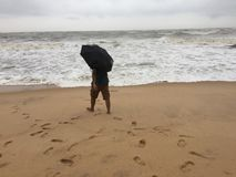 A young man venturing into the sea with an umbrella. At the beaches of Kundapura Stock Photo
