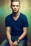 Young man with very handsome face in blue t-shirt. Portrait of a young man with very handsome face in blue casual t-shirt and stylish haircut posing over golden Royalty Free Stock Photo