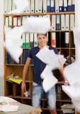 Young man in very messy office with documents flying Stock Image