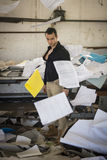 Young man in very messy office with documents flying Stock Images