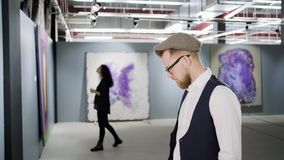 People are examining pictures in hall of modern art gallery, man and woman. Young man is viewing abstract canvas in contemporary art museum. Woman is enjoying stock video footage