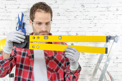 Young man viewing a spirit level,  to read the position of the Royalty Free Stock Images