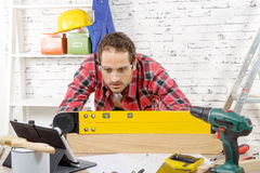 Young man viewing a spirit level,  to read the position of the Royalty Free Stock Photos