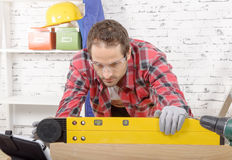 Young man viewing a spirit level Royalty Free Stock Photos