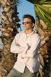 Young Man Viewing Sunset. A high school boy standing in the seabreeze watching a Florida sunset flanked by palm trees Royalty Free Stock Images