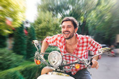 Young man on vintage old-style scooter with motion blur Royalty Free Stock Photo