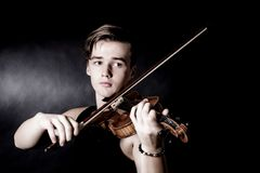Young man play violin on dark background. Young man with violin on dark background Stock Photos