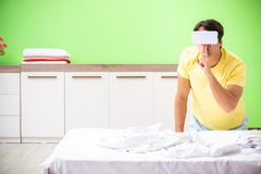 The young man with virtual glasses in the bedroom. Young man with virtual glasses in the bedroom royalty free stock images