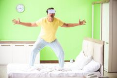 The young man with virtual glasses in the bedroom. Young man with virtual glasses in the bedroom stock photo