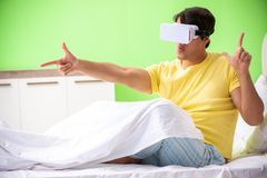 The young man with virtual glasses in the bedroom. Young man with virtual glasses in the bedroom royalty free stock image