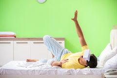 The young man with virtual glasses in the bedroom. Young man with virtual glasses in the bedroom stock image
