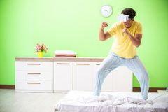 The young man with virtual glasses in the bedroom. Young man with virtual glasses in the bedroom royalty free stock photo