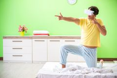 The young man with virtual glasses in the bedroom. Young man with virtual glasses in the bedroom royalty free stock photos