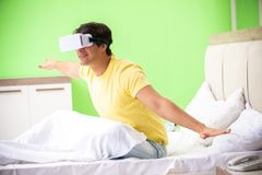 The young man with virtual glasses in the bedroom. Young man with virtual glasses in the bedroom royalty free stock photography
