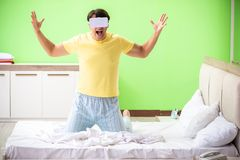 The young man with virtual glasses in the bedroom. Young man with virtual glasses in the bedroom stock photography