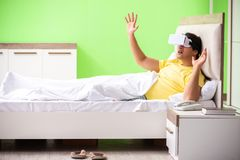 The young man with virtual glasses in the bedroom. Young man with virtual glasses in the bedroom stock photos