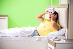 The young man with virtual glasses in the bedroom. Young man with virtual glasses in the bedroom stock images