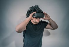 Young man with virtual reality glasses. Modern technologies. Image contains excessive noise, film grain, compression artifacts. And posterization due to special stock photo