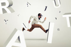 Young man in virtual reality glasses running between 3d letters Royalty Free Stock Photo