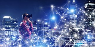 Guy wearing checked shirt and virtual mask holding his hand on chin. Young man with virtual reality headset or 3d glasses among connection lines Royalty Free Stock Photography