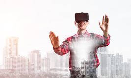 Guy wearing checked shirt and virtual mask stretching hands and trying to concentrate. Young man with virtual reality headset or 3d glasses over cityscape Stock Photos