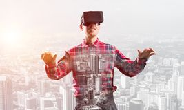 Guy wearing checked shirt and virtual mask stretching hands and trying to concentrate. Young man with virtual reality headset or 3d glasses over cityscape Stock Image