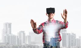 Guy wearing checked shirt and virtual mask stretching hands and trying to concentrate. Young man with virtual reality headset or 3d glasses over cityscape Royalty Free Stock Photos