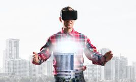 Guy wearing checked shirt and virtual mask stretching hands and trying to concentrate. Young man with virtual reality headset or 3d glasses over cityscape Stock Photography