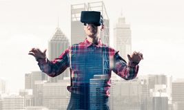 Guy wearing checked shirt and virtual mask stretching hands and Stock Photos