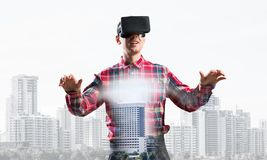 Guy wearing checked shirt and virtual mask stretching hands and trying to concentrate. Young man with virtual reality headset or 3d glasses over cityscape Royalty Free Stock Images