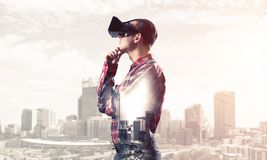 Guy wearing checked shirt and virtual mask with hand on chin. Young man with virtual reality headset or 3d glasses over cityscape background Stock Photo
