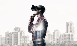 Guy wearing checked shirt and virtual mask with hand on chin. Young man with virtual reality headset or 3d glasses over cityscape background Royalty Free Stock Photo