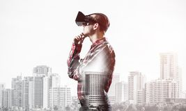 Guy wearing checked shirt and virtual mask with hand on chin. Young man with virtual reality headset or 3d glasses over cityscape background Stock Photos