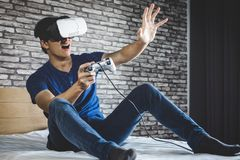 Young man in virtual reality headset or 3d glasses playing video. Game and pointing in the air, gaming and technology concept stock image