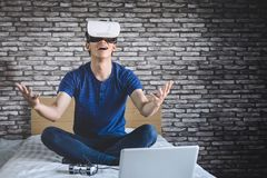 Young man in virtual reality headset or 3d glasses playing video. Game and pointing in the air, gaming and technology concept royalty free stock photo