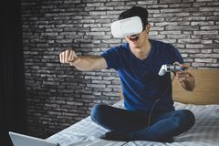 Young man in virtual reality headset or 3d glasses playing video. Game and pointing in the air, gaming and technology concept royalty free stock image