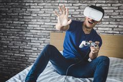 Young man in virtual reality headset or 3d glasses playing video. Game and pointing in the air, gaming and technology concept stock photo