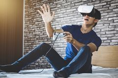 Young man in virtual reality headset or 3d glasses playing video. Game and pointing in the air, gaming and technology concept royalty free stock photos