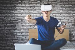 Young man in virtual reality headset or 3d glasses playing video. Game and pointing in the air, gaming and technology concept stock photos