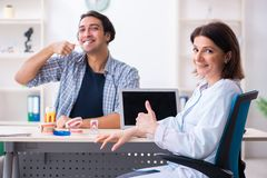 Young man visiting female doctor stomatologist. The young men visiting female doctor stomatologist royalty free stock image