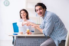 Young man visiting female doctor stomatologist. The young men visiting female doctor stomatologist stock photo